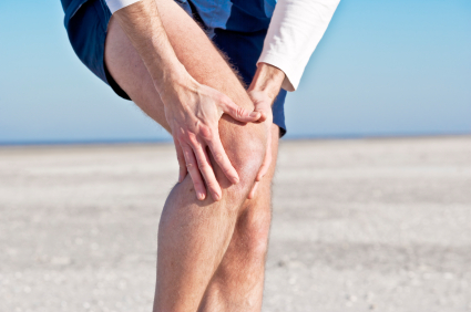 man holding knee to represent knee pain.