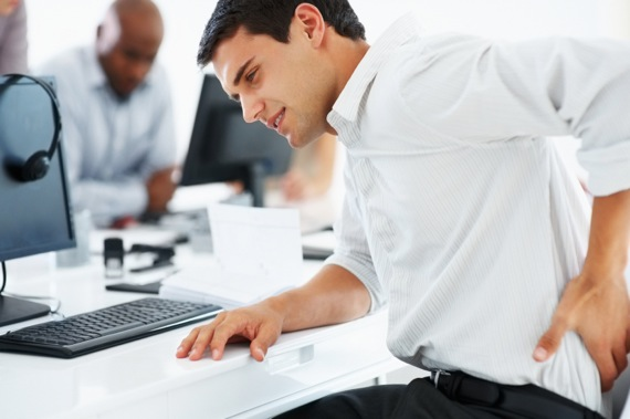 Man wearing white shirt in an office putting his left hand on his back to represent back pain.