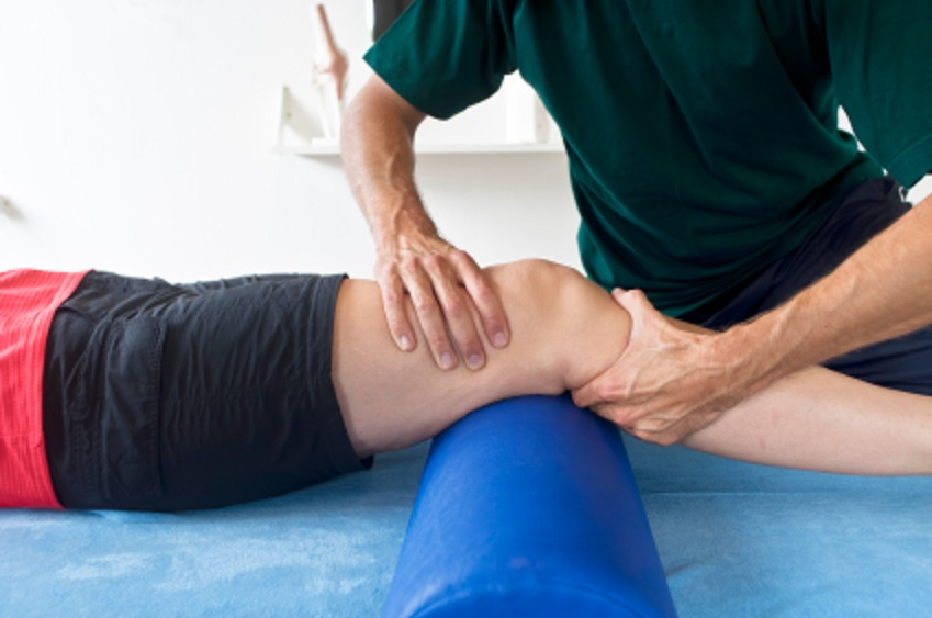 Leg placed on a roll cushion where leg joint is with a pair of hands giving a massage to the knee.