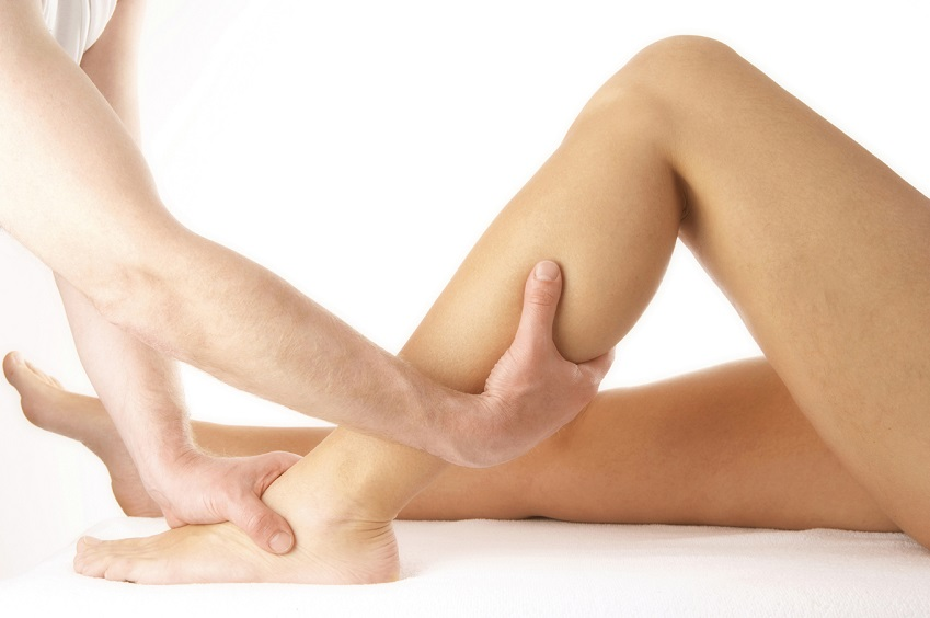 Close up of someones Hands giving someones leg physoptherapy treatment.