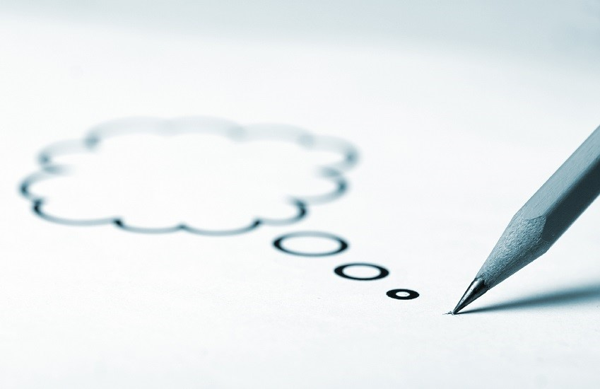 Drawing of cloud speech bubble on a piece of paper.
