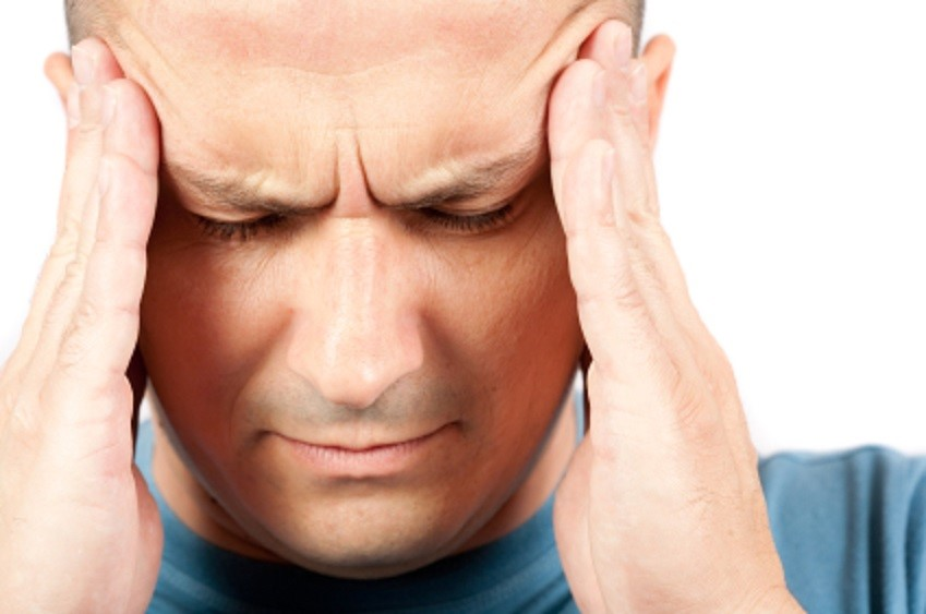 Man putting his hands on his head and looking in pain to represent a headache.