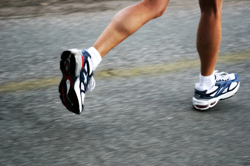 Close up of a persons legs, wearing white trainers running on a road.