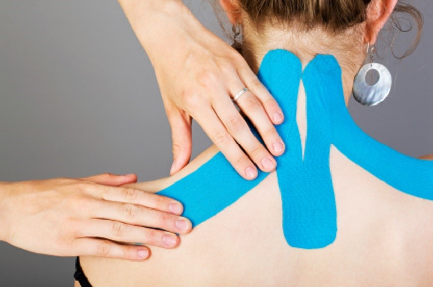 Woman having blue Kinesio tape put on her neck.