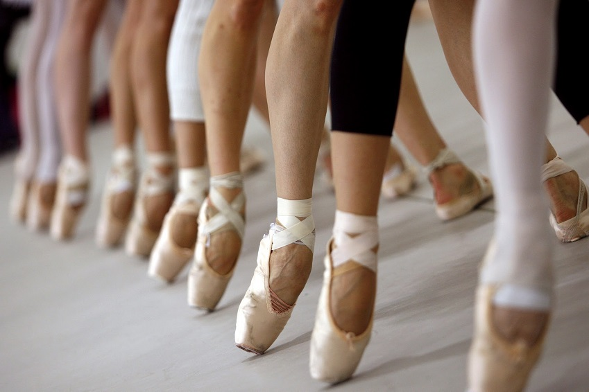 Group of balley dancers legs with end of their foot touching the floor.