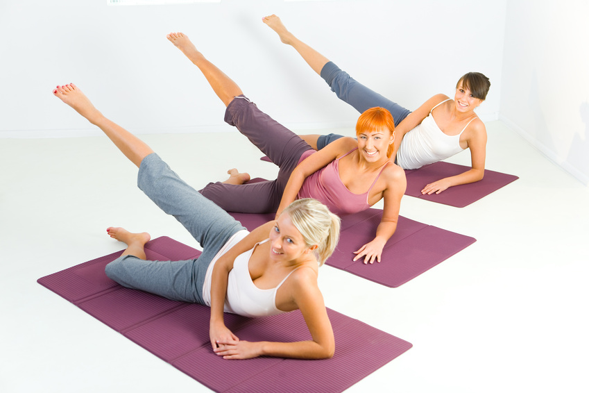 Three women lying on their side on a purple mat while stretching their right leg in the air.