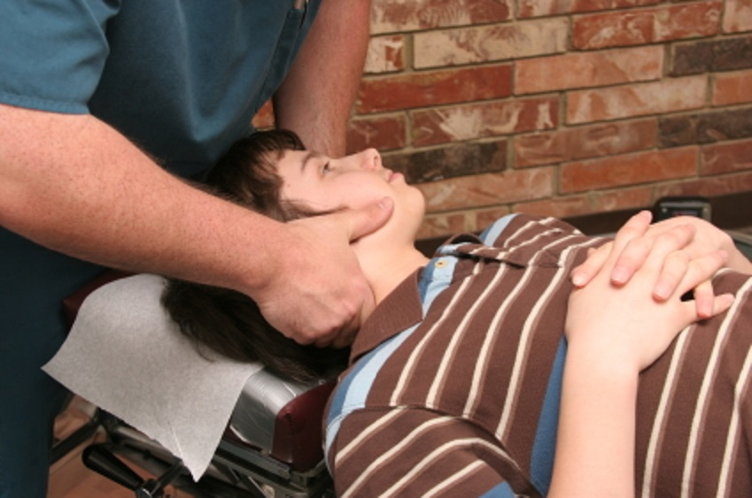 Boy lying on a bed with therapist giving treatment around the jaw.
